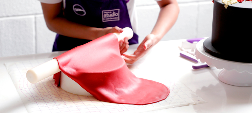 طريقة تغطية الكيك بعجينة السكر: وضع عجينة السكر على فرادة العجين ونقلها إلى الكيك