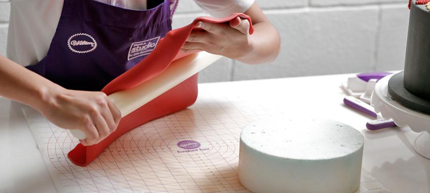 طريقة تغطية الكيك بعجينة السكر: رفع عجينة السكر وتغليف الكيك بها